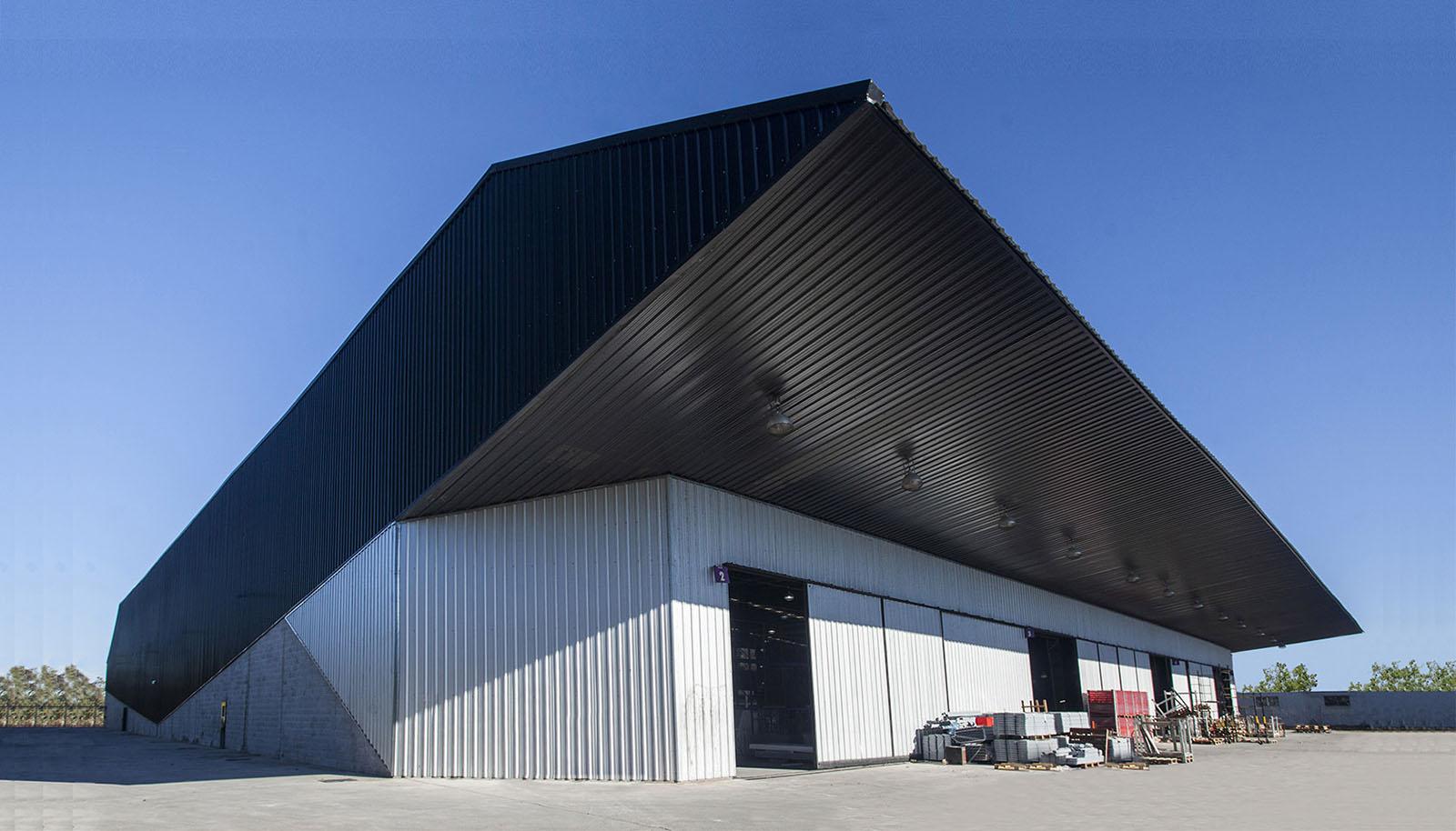 Foto contra frente fabrica arquitectura contemporánea industrial, cubierta de chapa, voladizo.