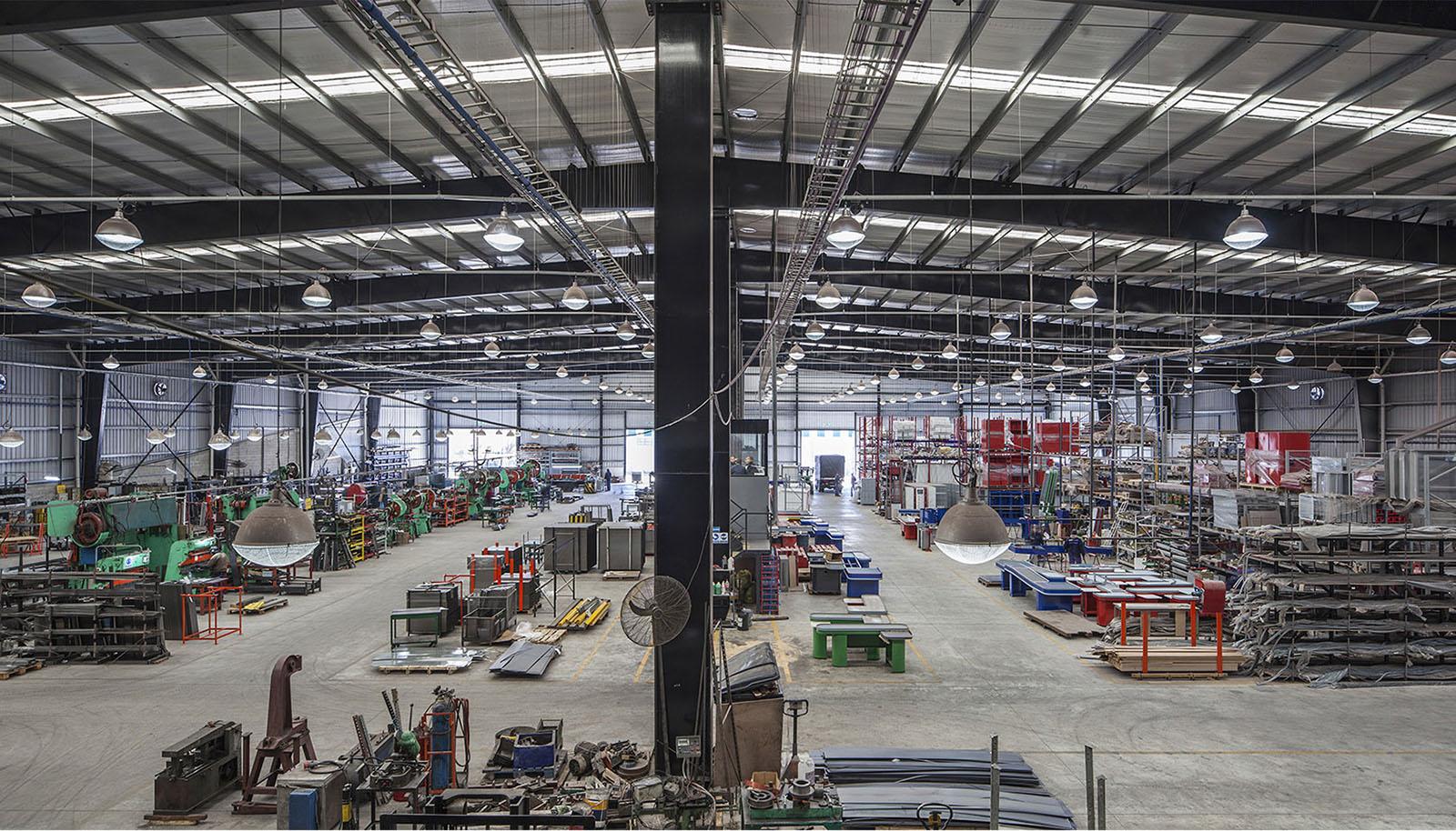foto vista interior espacio de producción de fábrica, iluminación, arquitectura en acero, grandes luces